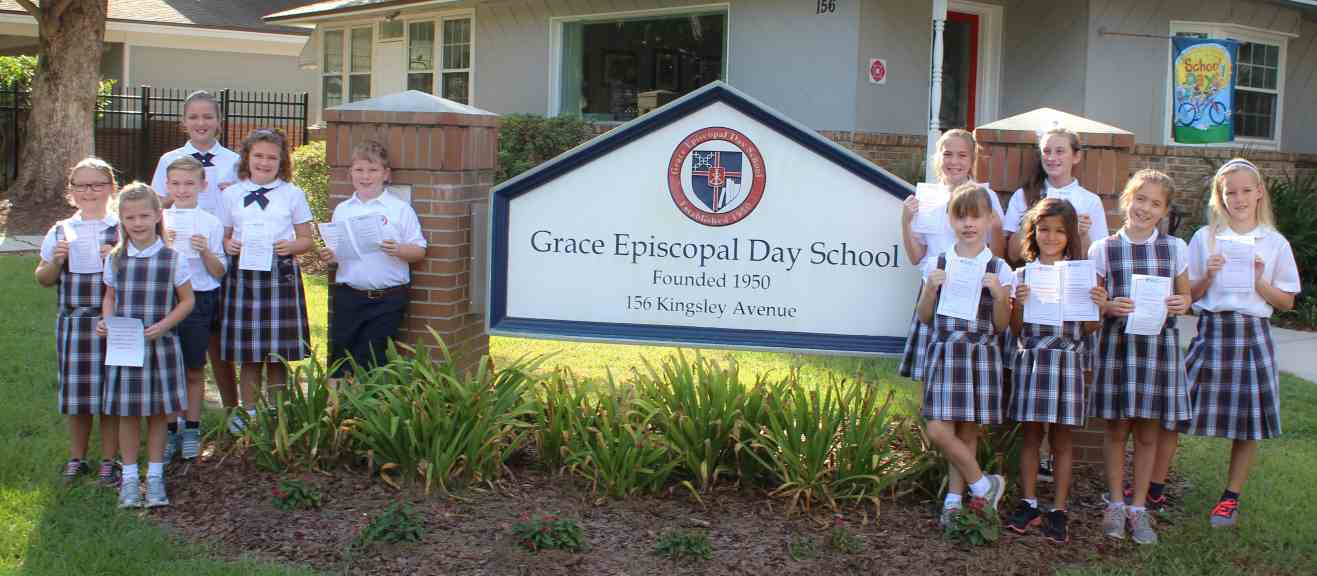 Children holding Fruit of Spirit certificates standing by the school sign