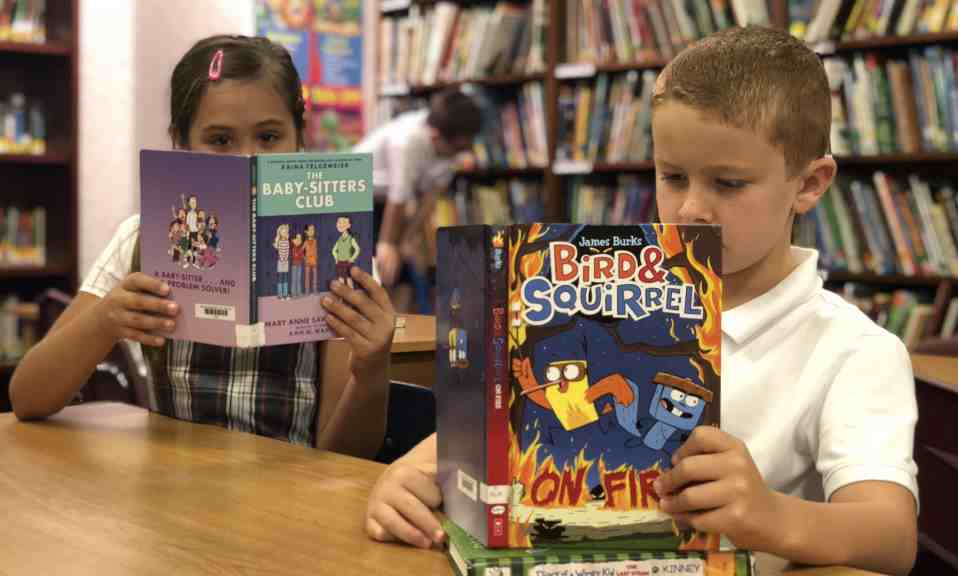 Two students reading books in library