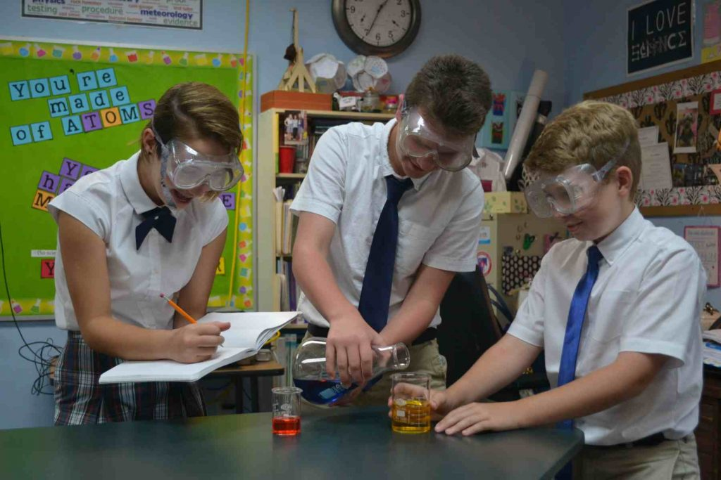 3 middle school students doing a science experiment