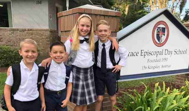 Three private christian school students standing in front of school sign