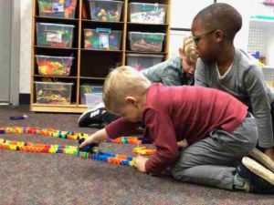 Two GEDS preschool students playing with LEGOs on the floor