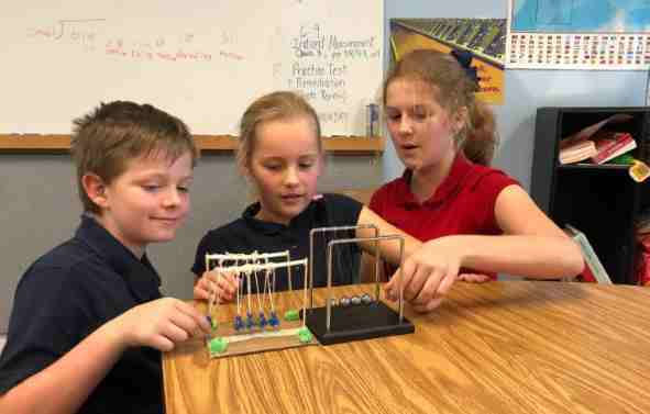 Three private christian school students and Newton's Cradle