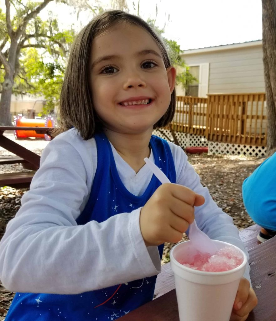 Kindergarten girl eating a snow cone