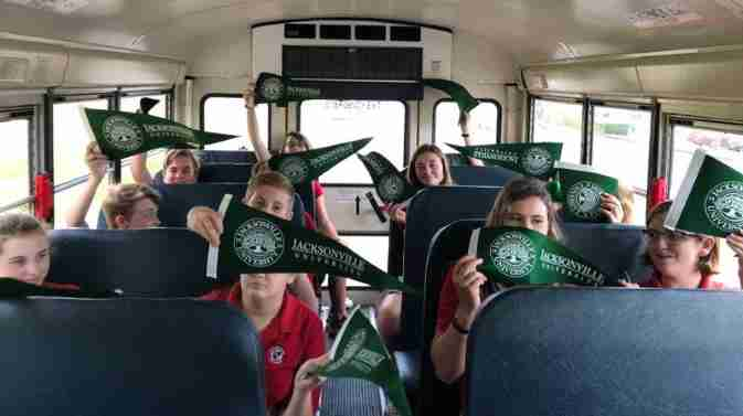 Middle School students riding bus holding JU flags