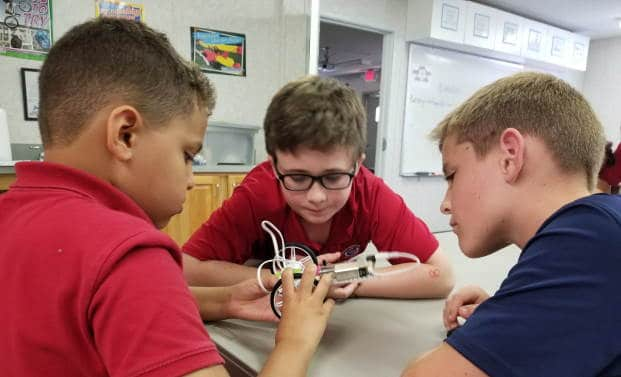 Three 4th grade boys working on building self-driving car