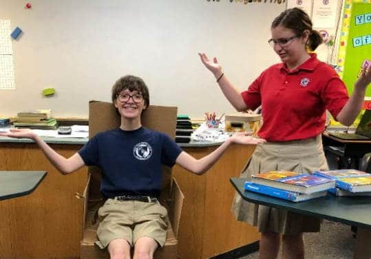 8th Grade Students showing off the chair they built