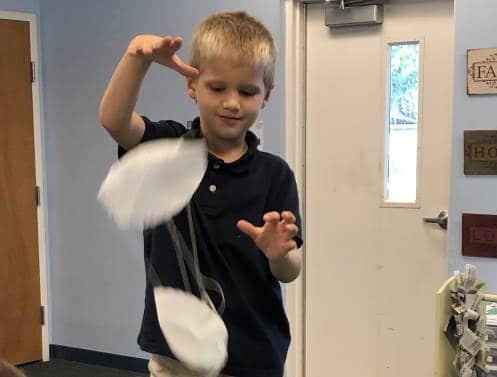 preschooler holding parachute