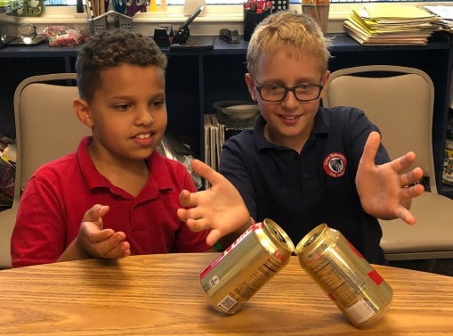 Two 4th grade boys balancing soda cans