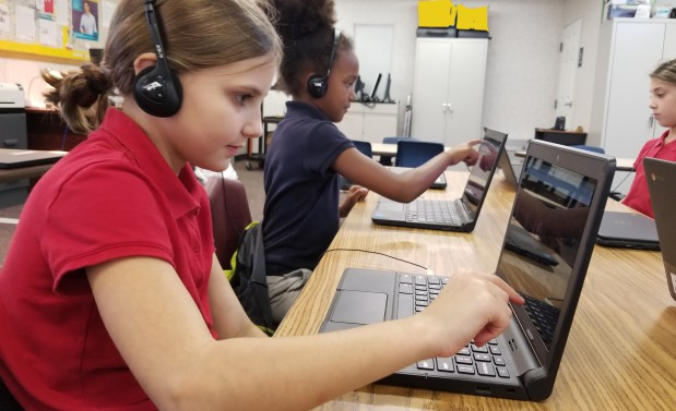 two young girls working on Chromebooks
