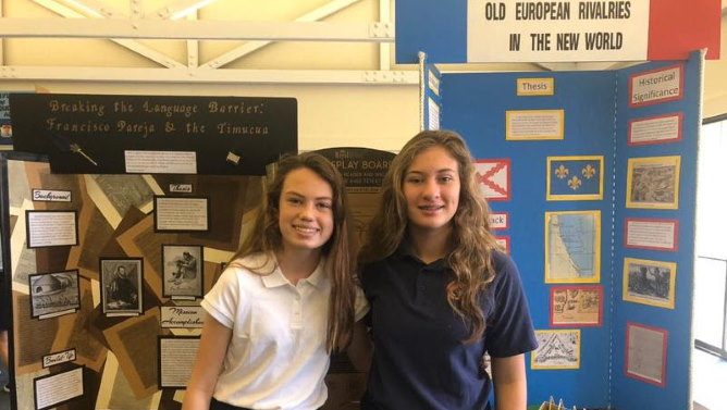 Two middle school girls standing in front of history projects