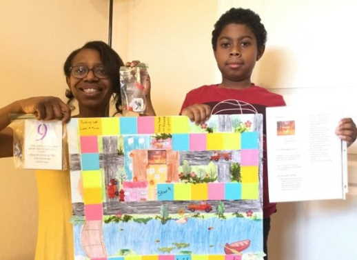 4th grader and parent holding poster board