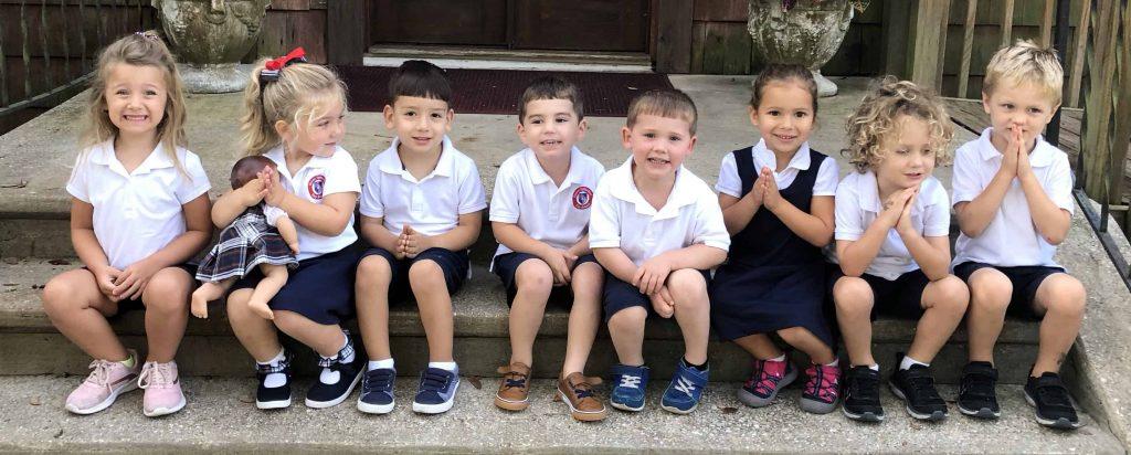 row of preschoolers sitting side by side