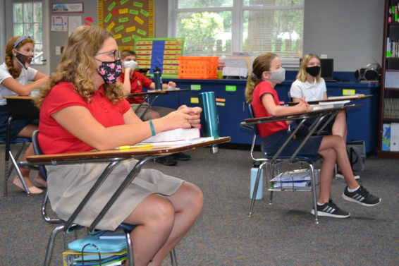 Middle Schoolers wearing masks sitting at their desks in the classroom