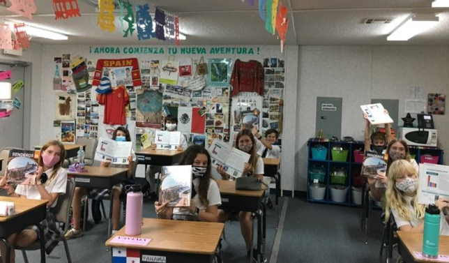 8th Graders in Spanish Class holding up new curriculum