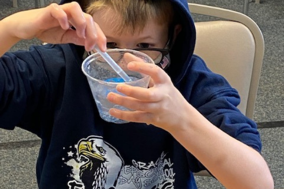 4th grade boy working with hydrophobic sand in a cup