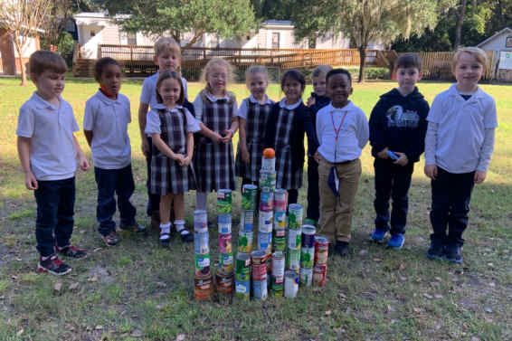 Kindergarten students posing with canned foods