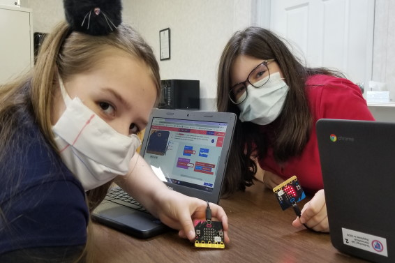 Two fifth grade girls holding microbits